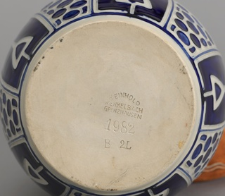 White ovoid jug with strap handle and spout with Jugendstil designs in cobalt blue.