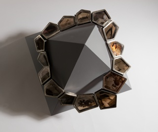 """Necklace comprised of 15 individual polygonic cells of different shapes and sizes, each containing a photographic transparency """"sandwiched"""" between two plates of clear mica and enclosed by silver frames."""