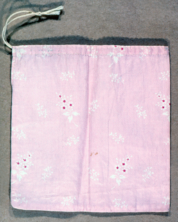 Plain square calico pocket with drawstring top. Fabric has a hatched pink ground with white and rose flowers.