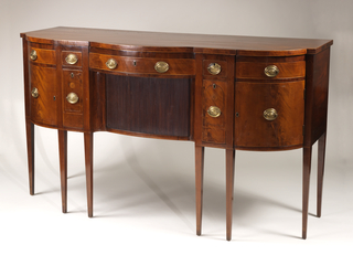 Shaped-front inlaid sideboard, tambour door below wide center drawer; square tapered legs; oval stamped brass drawer pulls.