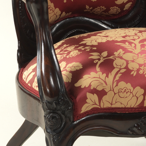 A) Upholstered, laminated rosewood back, topped by carved flowers-and-fruit garland.  Back frame formed of inverted U-shaped scroll at top and serpentine section at bottom.  Serpentine arms join back frame with scroll.  Upholstered spring seat on rosewood frame; serpentine seat front with carved flowers in center and at join of arms and forelegs.  Cabriole forelegs with carved acanthus leaf between small scrolls on foot; reverse curve back back legs; casters.  B) The same.