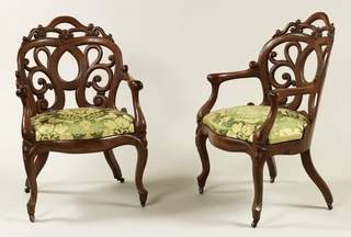 Pair of armchairs (a,b). Each chair with shaped openwork back, curved in plan; serpentine arms join back to scrolled front of seat; cabriole front legs, curved and splayed rear legs, all fitted with castors. Seat upholstered in green and cream colored fabric.