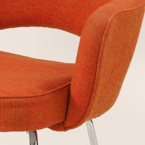 Curved back, arched at bottom, continuing into armrests surounding roughly square seat mounted on four chromed tubular steel legs with circular foot pads; back, armrests, and seat upholstered in orange and yellow woven fabric.