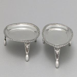 Oval shape on three piereced legs and ball feet; cast ornamental border in leaf design.