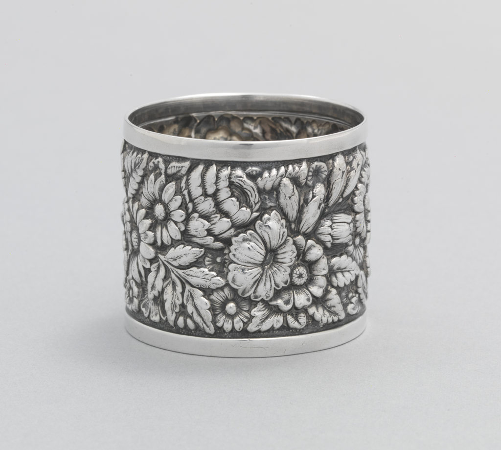 Small cylindrical cup with straight sides repoussé and chased all over with  flowers between plain bands at foot and rim.