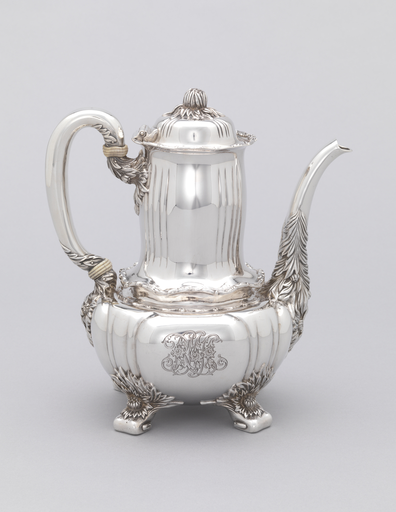 """Reeded globular body, engraved with foliate monogram """"RMA"""", rising to tall slightly bulging cylindrical neck with wavy rim; loop handle with ivory insulators on one side, and long curved spout heavily decorated with chrysanthemums and foliage opposite; base with four foliate feet. Slightly domed and reeded lid with flower bud knop."""