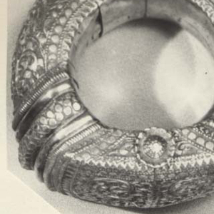 Hinged anklet closing with a silver pin.  Part of anklet is semicircular  and part flattened.  Decoration of curving stems with leaves and bands of line-and-circle ornament.  Hollow silver filled with plaster.  a = anklet, b= pin.