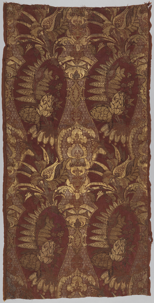 Two side-by-side repeats of exotic foliage within a curving border in gold metallic brocade on a plum-colored ground. The repeats give the impression of a central vase or columnar form, but the design is not symmetrical.