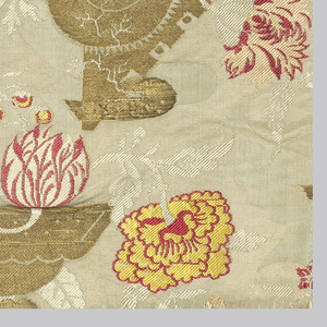 Seven fragments of textile panel, originally made up of three widths of material, edged with narrow strip of brocade with blue ground and backed with blue silk.  White satin ground with gold, red, yellow and white brocade. Irregular-shaped vessels from which flowers emerge.