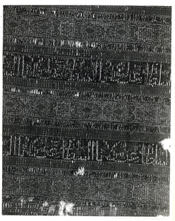 """Fragment of woven silk with alternating horizontal bands of red and blue, with narrower guard stripes between. The red bands contain patterns of eight-pointed stars and flowers; the blue bands contain lines of kufic script, translated as """"Glory to our master the Sultan.""""  In red, blue, yellow, green, and white."""