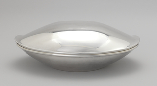 Oval dish with curved sides everted toward rolled plain lip. Flat base section. Domed cover with similar shape; curved dome flares outward gently at lip to form small opening at long ends of bowl. Lower bowl with raised lip section at sides into which similar sections of cover fit when closed.