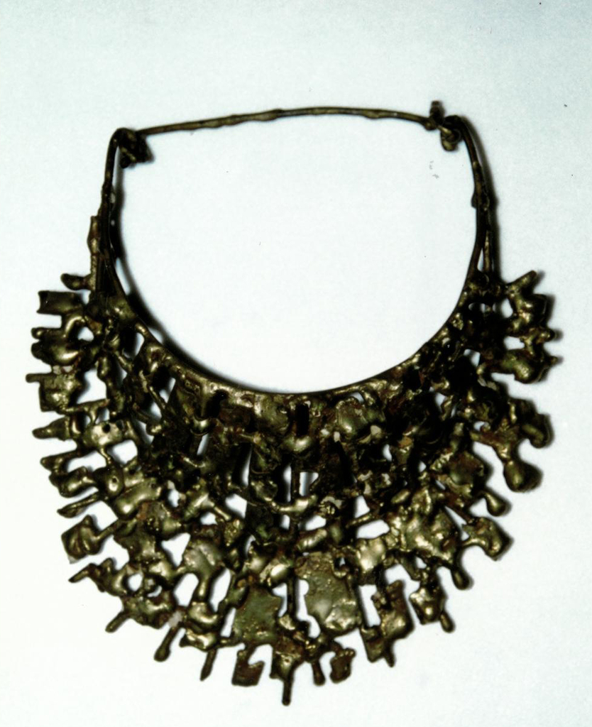 Cast bib necklace composed of one piece of brass shaped into random striations and biomorphic forms, some look melted.