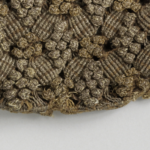 Unlined drawstring bag with two different macramé knots used to produce a lattice-like pattern with diamond-shaped clusters of of tiny balls, in gold and silver metallic yarns.