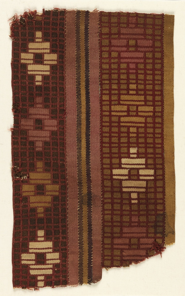 Fragment of a mantle with two wide patterned bands, one brown, one ocher, separated by narrow stripes of solid pink, brown and ochre. The patterned bands are divided into small rectagles by a grid of red, with large star-like stepped motifs in pink, tan and off-white.