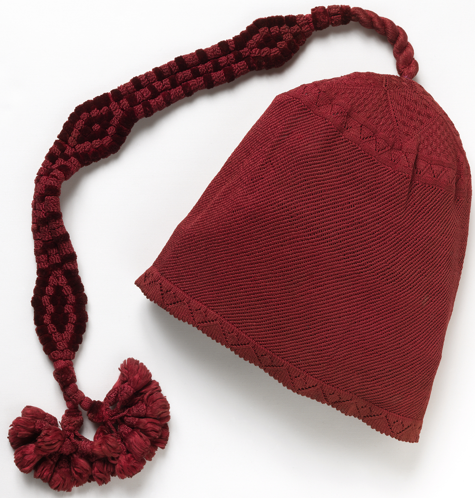 Dark red knitted silk cap with diagonally ribbed body, and crown with a star-shaped area of varied knitting patterns. With very long ornament of silk cords and chenille, forming three lozenge shapes and terminating in two tassels.
