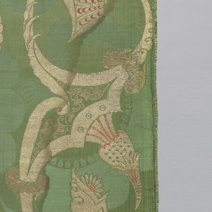 Piece of brocaded silk with a 'bizarre' style design of exaggerated curvilinear shapes piercing and being pierced by foliate forms. In gold and silver thread with red accents on a green ground.