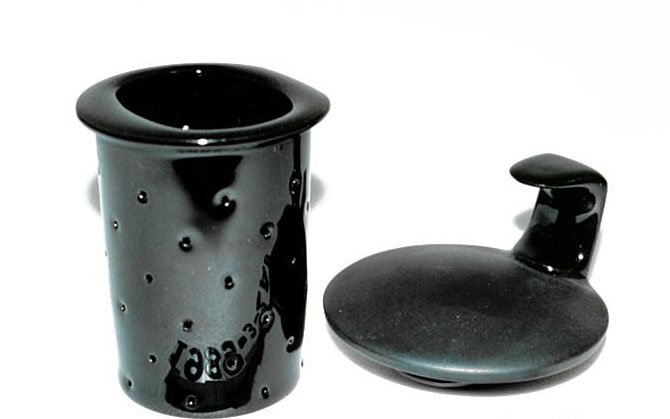 Black glazed porcelain cup pierced with holes and everted lip.