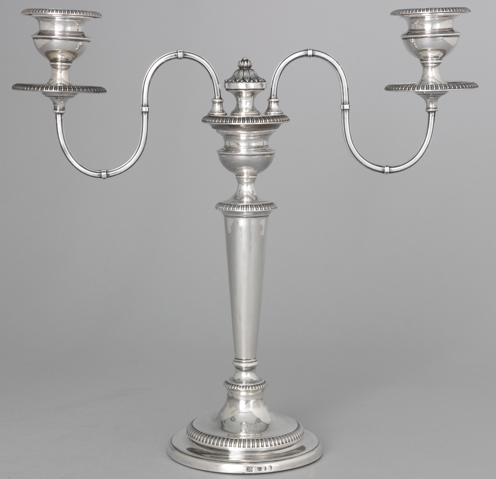 Pair of George II chamber candlesticks designed by William Cafe (active ca. 1757-died 1802-1811); each with circular plate with lip-curved edge and reeded rim; scroll handle with thumbplate terminating in ribbed scroll; handle fitted to hold plain conical extinguisher with reeded edge and baluster finial; candle socket raised on baluster shaft and with flanged nozzle permanently affixed; on source of each and on extinguisher of each is engraved an unidentifiable crest.