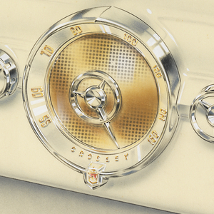 White molded case vacuum tube radio featuring center pointer dial for tuner, flanked by volume and tuning control knobs.  Design is reminiscent of automobile dashboards of the era.  Knobs, center dial pointer and bezel feature chrome-like surface.  Dial appears to be clear lucite with reverse painting.