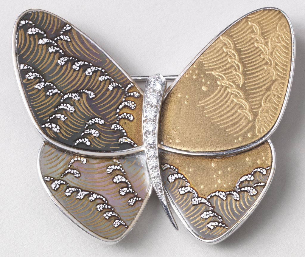 Abstract butterfly form comprising simple, curved body studded with small diamonds, flanked by wings with mother-of-pearl and egg shell decoration depicting stylized ocean waves in tones of gold, brown, black and white.