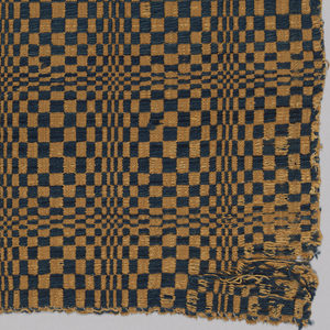 Fragment of an overshot coverlet with an overall grid format containing a checkboard of tobacco brown and blue squares. The illusion of spheres emerging from the surface is created by varying the height and width of the blocks.