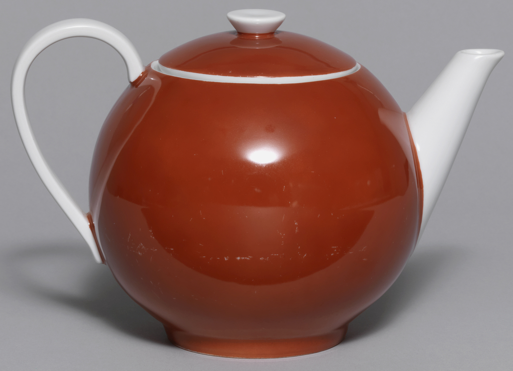 Red globular teapot with long white tapering cylindrical spout; domed lid with inverted conical white knop; white loop handle.