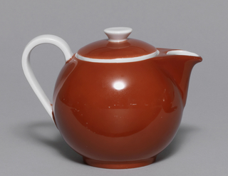 Red globular jug with short spout; domed lid with inverted conical white knop; white loop handle.