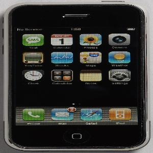 """Flat rectangular aluminum and plastic body with rounded corners; front composed of large glass touch-screen with black bands at top and bottom, showing colorful application """"widgets"""" (symbols) or functions (number pad, keyboard) when phone is on; dark when off. Volume and ring-tone controls on left side; on/off button on top right; function control (dimple-like depression) on bottom front. On back: cameral lense in upper right corner; Apple logo; black plastic panel at bottom."""