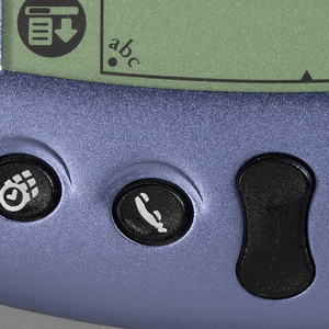 Metalic blue, flat rectangular housing (a) with curved flared bottom; the face dominated by a rectangular screen with four icons on right and left at bottom third; four black function buttons flanking black scroll button at bottom of housing; thin cylindrical back stylus (b), stored in right side of housing.