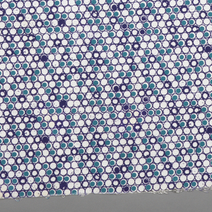 Design of small tangent circles, some open, some partially filled and some completely filled with color. In shades of blue on a white ground.