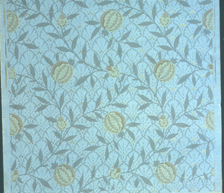 Full width, the end of a roll, giving one and one-half repeats of a pattern of serpentine vine, with conventionalized fruit, against a conventionalized all-over background of simple foliate forms with accents of gold circles. Paper embossed in vertical ribbing. Printed in tans, blue-greens and gold.