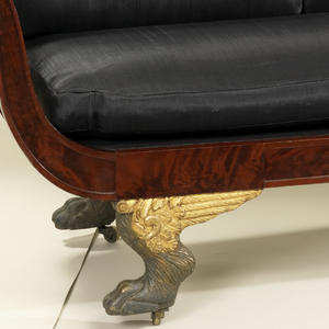 Frame with outward scroll arms with open lyre-form splats mounted sideways; gilt-wood winged paw feet. Upholstery replaced, 2011.