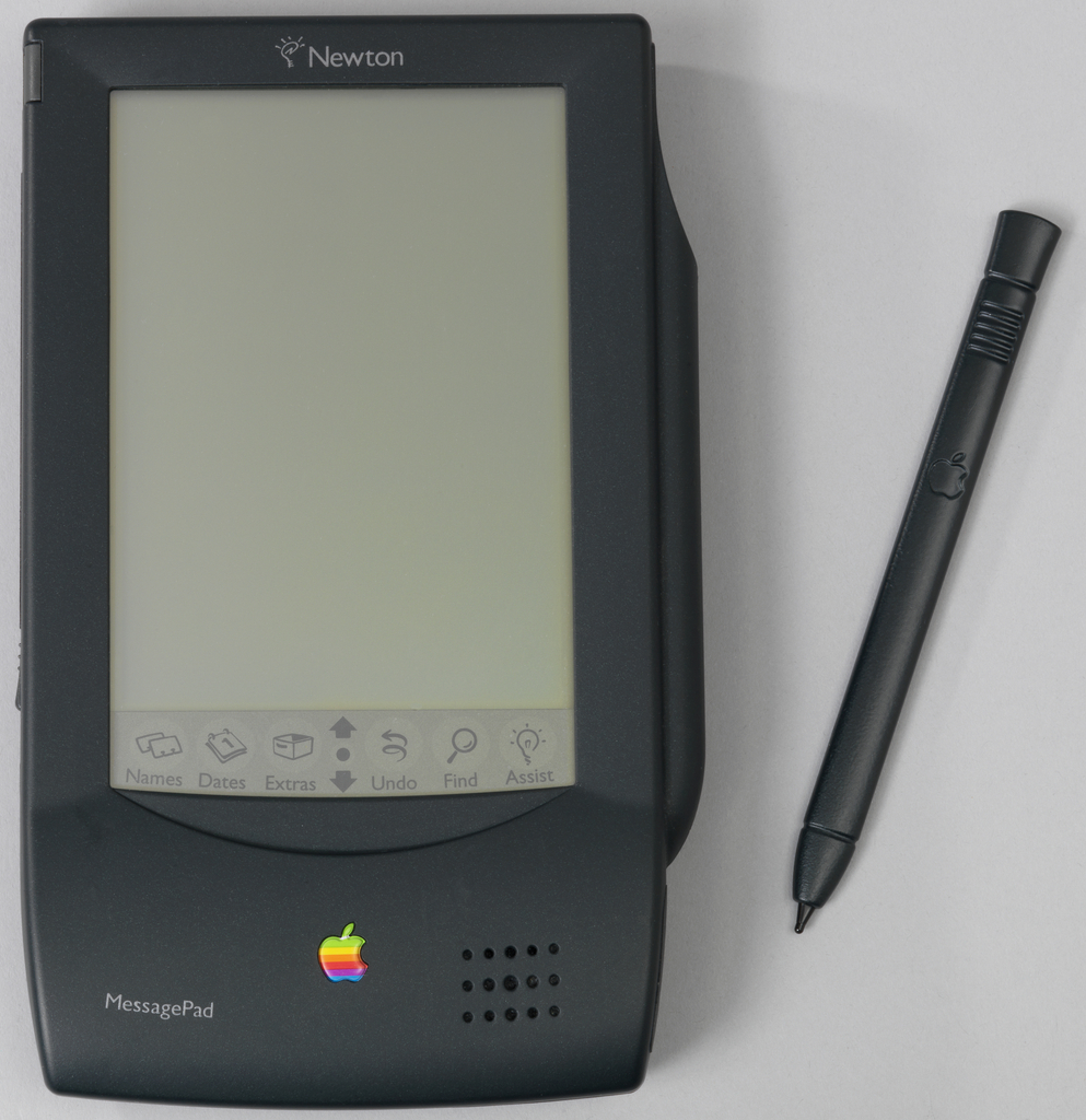 Gray, rectangular contoured housing (a) having large display screen on front with function symbols at bottom; stylus (b) housed in holder on right side. Colored Apple logo on housing below screen.