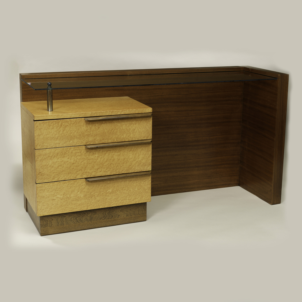 "Rectilinear wood and glass form; back and right side of dark walnut; 3-drawer unit of light wood on left, each drawer with a long horizontal dark wood handle; planar, ""floating"" glass top set into back and right side, attached to top of drawer unit by a cylindrical metal post at front left corner."