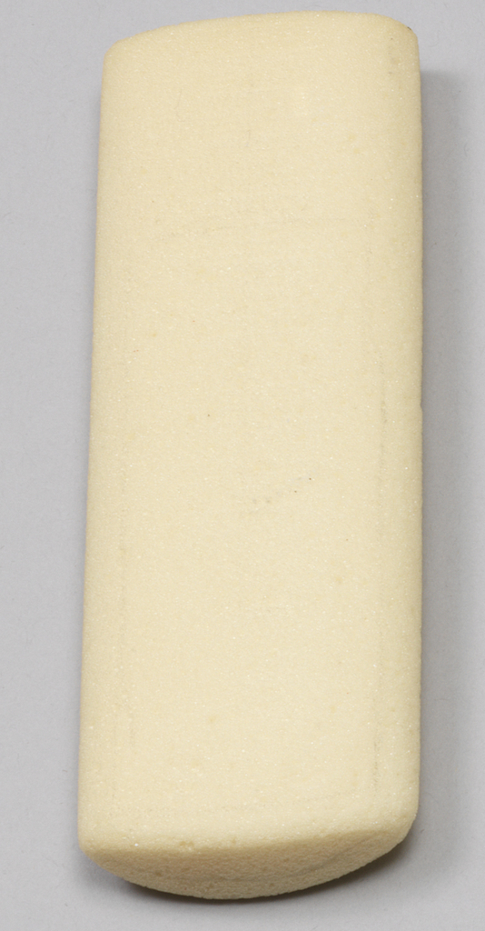 White foam somewhat rectangular form with flat side and rounded side.