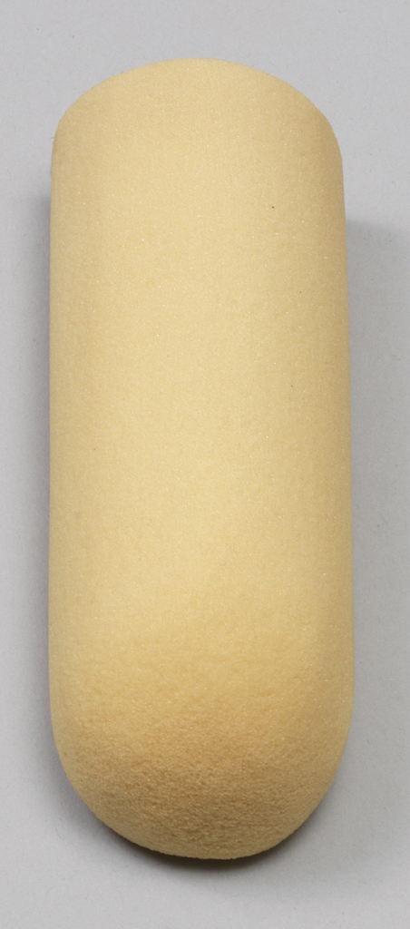 Cyndrically-shaped piece of beige foam with rounded bottom.