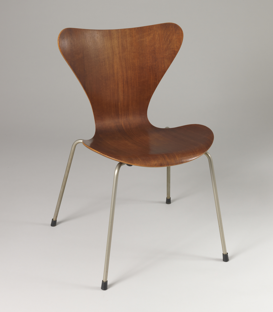 Continous bentwood sheet forming hour glass-shaped back and seat mounted on base of four thin cylindrical steel legs; black caps on feet.