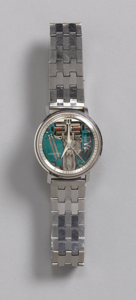 Stainless steel circular watch; clear crystal over thin circular chapter ring with lines and luminous dots denoting minutes and hours; thin tapered white hands; tuning fork and electronic works visible under crystal.