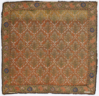 Square panel or cover trimmed on all sides with a woven border. The field has an orange-red ground with a lattice formed by spiraling white bands. Within each diamond formed by the lattice is a flowering plant. The border has a meandering vine with small white and blue flowers and red carnations.