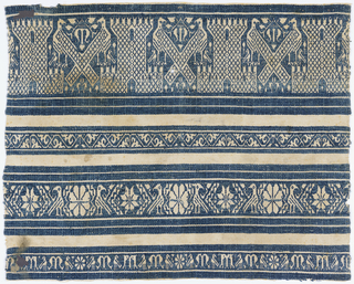 Perugia towel end with blue bands showing birds, flowers, castles, and the letter M.