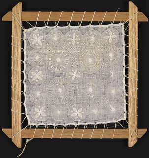 Wooden stretcher with work in process of 21 circles embroidered on a plain weave foundation. After the filling embroidery was complete, the work would be cut from the ground cloth to form a lace-like textile called Tenerife.