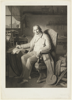 Interior, with a man seated in an armchair, his body turned toward the left, looking out at the viewer. Model of loom at left.