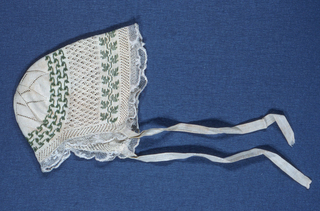 Infant's bonnet in knitted white silk with green glass beads in a vine pattern around the crown of the head and along the front edge. With lace edging, ivory silk ribbons to tie.