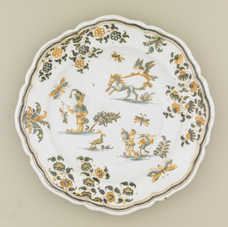 Circular form with scalloped edge; decorated with flowers and foliage, Callot-style figures on staggered terraces. Green and ochre on white ground.