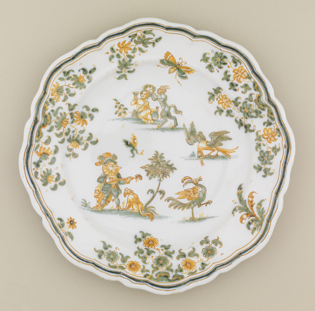 Circular form with scalloped edge; decorated with flowers and foliage, mythological Callot-esque figures. Green and ochre on white ground.