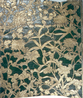 Flowering vine and possibly bamboo plant, with snail, grasshopper and dragon fly.  Embossed and printed in gold on deep green ground.