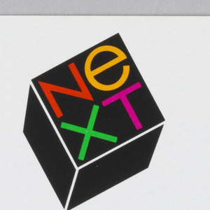 Company sticker imprinted with the NeXT logo, a cube in black on which is printed the four letters of company in two lines, in red, orange, green, and pink respectively.  Below cube  the name and address of firm.