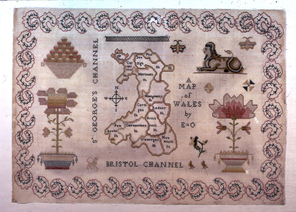 A map of Wales with detached plants, a butterfly and a sphinx.