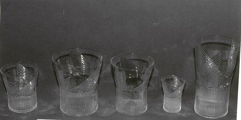Mold-blown glass with vertical ridge pattern on wide cylindrical stem.  Ridge pattern continues on vessel in a triangular format (3).  Highball.