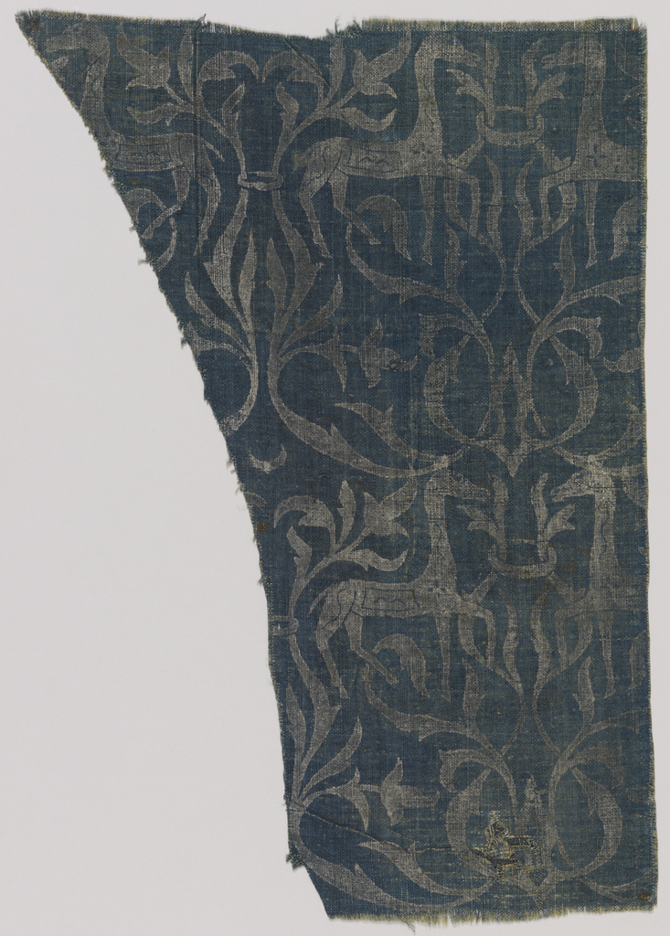 Coarse dark blue linen ground with design printed in silver. Paired confronted deer (or horses) with flanking foliate scrolls.